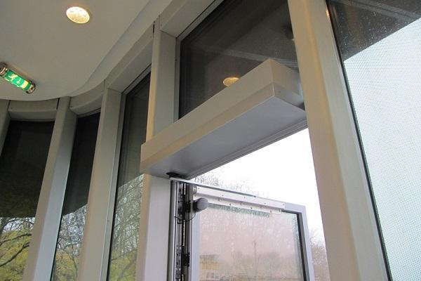 Hinged door operator on large glass door